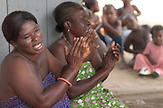 "Women chanting during a ""coming out"" ceremony at a fetish shrine in Aflao, Volta Region, Eastern Ghana. A woman was released after spending three months in a small, dark room, hoping that she'd then be able to find a husband. Despite most Ghanaians being adamant followers of christianism or islam, many of them still maintain traditional beliefs. When facing a problem of any nature, some people will visit a local fetish shrine, looking for help. The main priest will consult the oracles and tell the person in need what has to be done for the problem to go away. People will typically be asked to ""serve"" the shrine for weeks, sometimes months, as their families pay the priest for their upkeep."