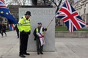 On the day that Prime Minister Theresa May's Meaningful Brexit vote is taken in the UK Parliament, a Leave supporter is spoken to by a Met Police officer beneath the statue of Winston Churchill in Parliament Square, on 15th January 2019, in Westminster, London, England.