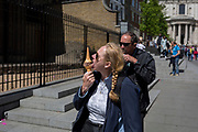A woman with a pigtail is enjoying a double-coned ice-cream in the City of London, on 14th May 2017, in London, England.