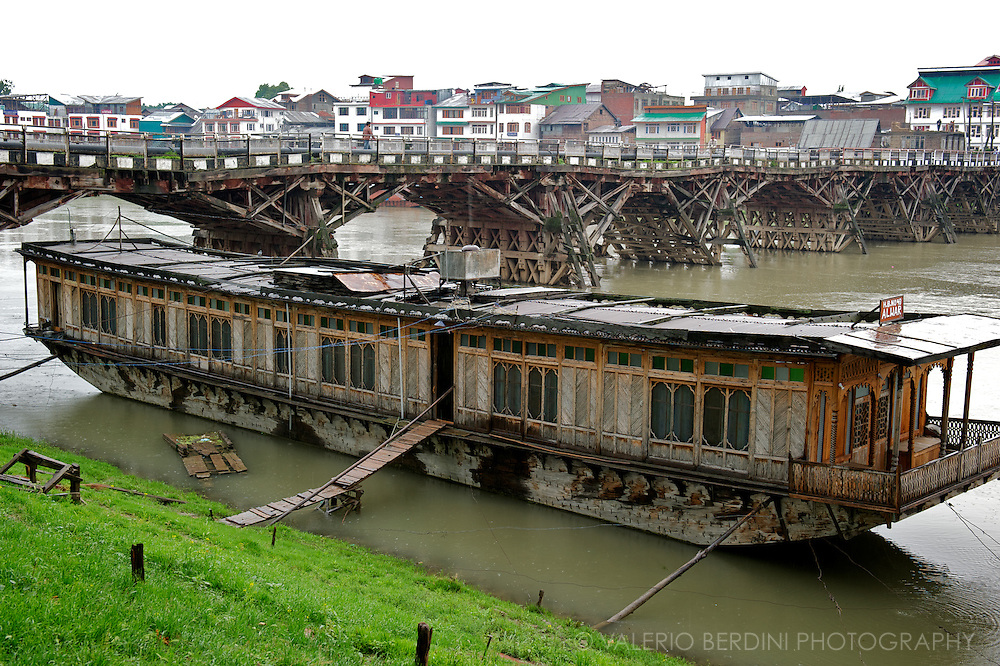 One of the several houseboats floating on the Jhelum river in Srinagar in front of one of the famous nine old bridges of the city.<br /> Kashmir. India