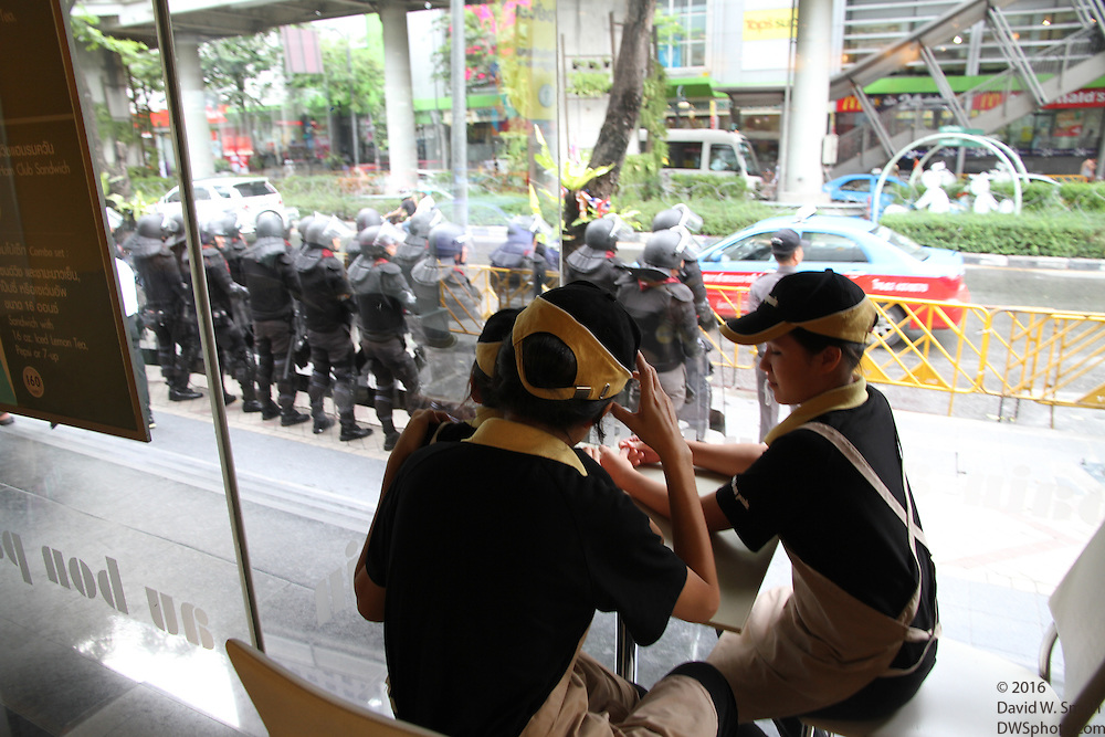 Restaurant staff watch as Thai police stand guard during the Red Shirts anti-government protest in the Silom area of Bangkok.