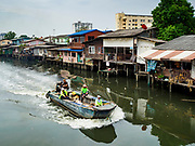 "22 MARCH 2018 - BANGKOK, THAILAND: City garbage haulers in a boat go past homes on Khlong Lat Phrao. Bangkok officials are evicting about 1,000 families who have set up homes along Khlong  Lat Phrao in Bangkok, the city says they are ""encroaching"" on the khlong. Although some of the families have been living along the khlong (Thai for ""canal"") for generations, they don't have title to the property, and the city considers them squatters. The city says the residents are being evicted so the city can build new embankments to control flooding. Most of the residents have agreed to leave, but negotiations over compensation are continuing for residents who can't afford to move.      PHOTO BY JACK KURTZ"