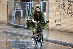 © Licensed to London News Pictures. 26/08/2018. London, UK. A woman cycles through wet and windy conditions at family day of the 2018 Notting Hill Carnival. Up to 1 million people are expected to attend this weekend's event that is one of the worlds largest street festivals. Photo credit: Ben Cawthra/LNP