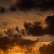 Light clouds are silhouette against a golden sky at sunset.