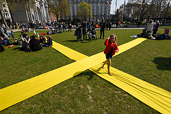 "© Licensed to London News Pictures. 15/04/2019. LONDON, UK.  A child runs across a giant X marked out on the park at Marble Arch as people surround Marble Arch taking part in ""London: International Rebellion"", a protest organised by Extinction Rebellion, demanding that governments take action against climate change.  Marble Arch, Oxford Circus, Piccadilly Circus, Waterloo Bridge and Parliament Square have been blocked by activists.  According to the organiser, similar protests are taking place in 80 other cities around the world.  Photo credit: Stephen Chung/LNP"