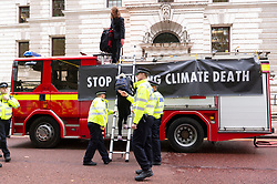 """© Licensed to London News Pictures. 03/10/2019. London, UK. Extinction Rebellion protesters are arrested by police after using a fire engine to spray the front of the Treasury building with fake blood. Extinction Rebellion said it wanted to highlight the """"inconsistency between the UK Government's insistence that the UK is a world leader in tackling climate breakdown, while pouring vast sums of money into fossil exploration and carbon-intensive projects"""". Photo credit: Ray Tang/LNP"""