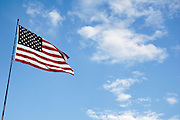 United states of America flag blowing in the wind with clouds and blue sky background