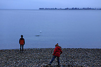Two young brother skipping stones across Lake Te Anau in Fiordland National Park, New Zealand