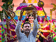 "22 OCTOBER 2015 - YANGON, MYANMAR:  A Hindu man makes an offering to Sri Kali temple in Yangon. A statue of the Goddess Durga is behind him. Navratri, literally ""nine nights"" is a Hindu festival devoted to the Goddess Durga. Navratri festival combines ritualistic puja (prayer) and fasting. Navratri in India follows the lunar calendar and is celebrated in September/October as Sharad Navratri. It's widely celebrated in countries in Southeast Asia that have large Hindu communities, including Myanmar (Burma). Many of Myanmar's Hindus are descendants of Indian civil servants and laborers who came to Myanmar when it was the British colony of Burma. PHOTO BY JACK KURTZ"