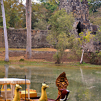 Kongkear Boats at Angkor Thom in Angkor Archaeological Park, Cambodia<br /> In 1177, the Cham (Champa was a former kingdom in present day Vietnam) used ships to conduct a surprise raid on the Khmer Empire&rsquo;s capital city. The following year, Jayavarman led counter attacks including a naval battle to defeat Jaya Indravarman IV. Featured on the prow of the battle boats were mythological beasts such as the nāga (right), the garuda (left) and a sea serpent called makara. These are small replicas of the Khmer king&rsquo;s fleet. The wooden Kongkear boats offer rides around the moat similar to a gondola. In the background is the gopura or gateway forming the southern entrance to Angkor Thom.
