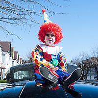 London, UK - 16 March 2014: Shaya, 4,  Dressed in a clown costume sits on a car during the festivity of Purim.