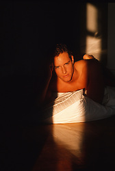 Man resting on the floor at home with a pillow during a sunset