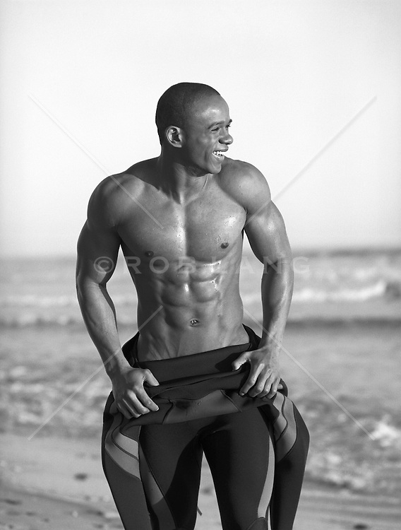 African American Man removing his wetsuit at the beach