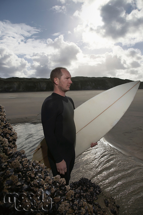 England Cornwall man holding surfboard standing by rocks on beach elevated view