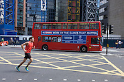 A mid-afternoon jogger runs over the junction of Bishopsgate as a London double-decker bus advertising Sky Sports drives south.
