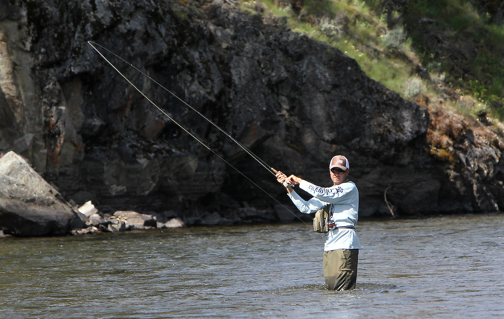 A fly fisherman casts his line in the Salmon River north of Stanley, ID in the Sawtooth Mountains on Monday July 15, 2013.