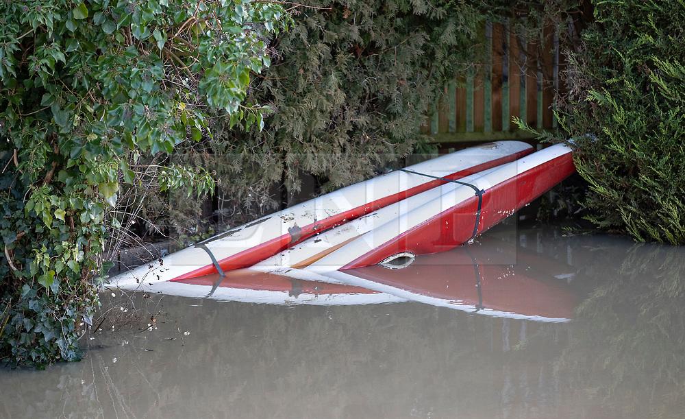 © Licensed to London News Pictures. 23/12/2019. Yalding, UK. Semi submerged canoes remain moored by a house on the river Beult  near Yalding, Kent. Flood levels have begun to recede in the centre of Yalding village. River levels are beginning to drop after days of heavy rain in the south. Photo credit: Peter Macdiarmid/LNP
