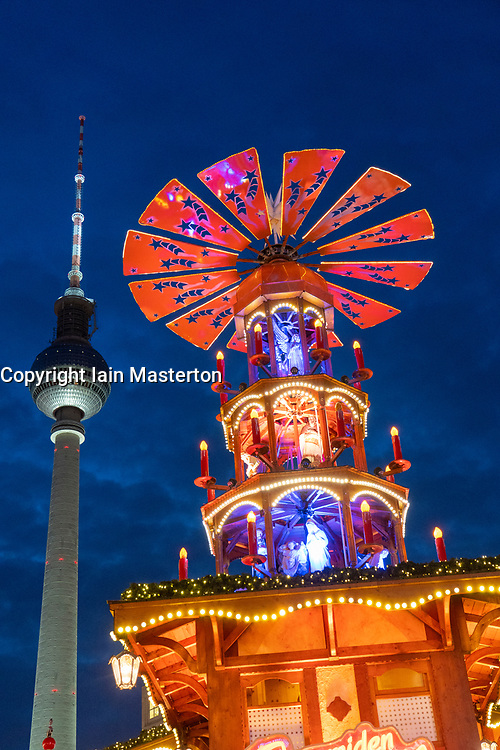 Berlin, Germany. 29 November, 2018.  The traditional colourful Pyramiden Treff or Pyramid meeting place contrasts with the Television Tower or Fernsehturm at the Christmas Market held at Alexanderplatz in Berlin, Germany.