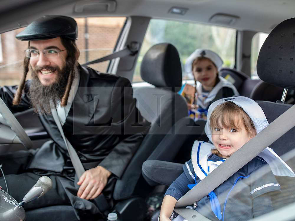 © Licensed to London News Pictures. 21/03/2019. London, UK. An Orthodox Jewish man and his children, in fancy dress, celebrate the festival of Purim on the streets of Stamford Hill in north London on 21 March 2019. Purim celebrates the miraculous salvation of the Jews from a genocidal plot in ancient Persia, documented in the Book of Esther. Traditionally the jewish community wear fancy dress and exchange gifts of food and drink. Photo credit: Rob Pinney/LNP
