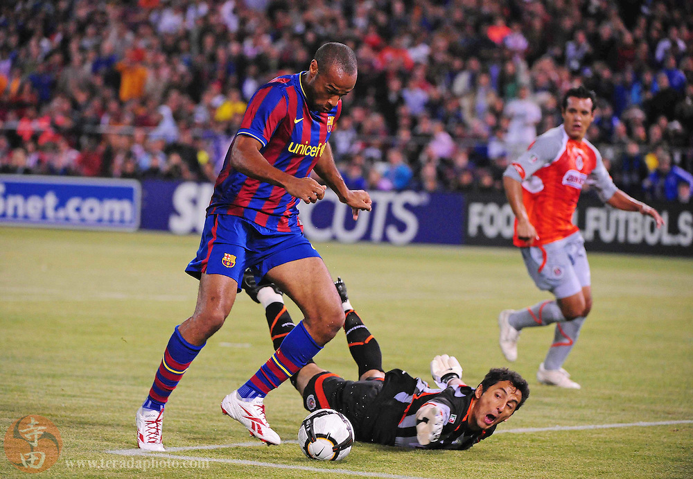 August 8, 2009; San Francisco, CA, USA; FC Barcelona forward Thierry Henry (left) shoots in front of Chivas de Guadalajara goalkeeper Luis Michel (center) during the first half in the Night of Champions international friendly contest at Candlestick Park. Henry missed the shot.