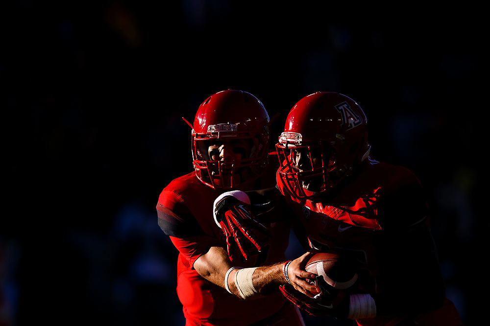 Arizona senior quarterback B.J. Denker (7) hands=-off the football to Arizona junior running back Ka'Deem Carey (25) during the third quarter. The No. 5 Oregon Ducks play the Arizona Wildcats at Arizona Stadium in Tucson, Ariz. on Nov. 23, 2013. (Ryan Kang/Emerald)