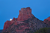 Courthouse Butte does its best to keep the moon from setting as the sun begins to illuminate the early morning sky. Sedona, Arizona.