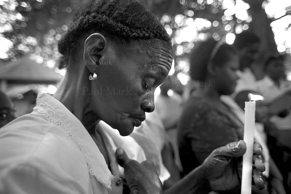 A widow at a mass held by displaced families in memory of the victims from theircommunity on the eve of their return journey to Cacarica, from where they were displaced by a joint Colombian military & paramilitary offensive three years previously. Their return marked the founding of the Peace Community of Cacarica. The Peace Communities are a strategy to allow civilian communities to remain on their lands which are in conflict zones. All their members pledge neutrality in the conflict, which means not collaborating with any armed grouping, including the State military forces. This policy of neutrality has often made the communities' members targets of the Army and paramilitary groups, who accuse the communities of collaborating with the guerrillas.