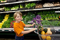 Portrait of a young boy with shopping cart in vegetable market