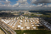 Miles of refinery and petroleum infrastructure stretch out along the Houston Ship Channel.  Houston's downtown appears faintly on the horizon.
