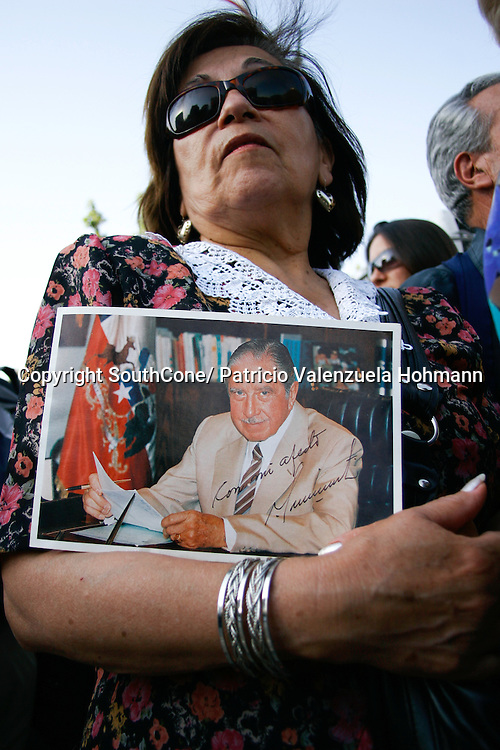 A woman holds a signed photograph of the dictator.<br /> December 2006, The Chilean Dictator Augusto Pinochet died in Santiago Chile. As news spread thousands went out the streets either to celebrate o mourn Pinochet who lead the 1973 coup that overthrew the democratically elected president Salvador Allende. Pinochet's 17 year regime killed and disappeared around 4.000 people, tortured and exile around 20.000. On 1989 he lost elections and democracy was regained. He died on late December 2006. December 2006, The Chilean Dictator Augusto Pinochet died in Santiago Chile. As news spread thousands went out the streets either to celebrate o mourn Pinochet who lead the 1973 coup that overthrew the democratically elected president Salvador Allende. Pinochet's 17 year December 2006, The Chilean Dictator Augusto Pinochet died in Santiago Chile. As news spread thousands went out the streets either to celebrate o mourn Pinochet who lead the 1973 coup that overthrew the democratically elected president Salvador Allende. Pinochet's 17 year.