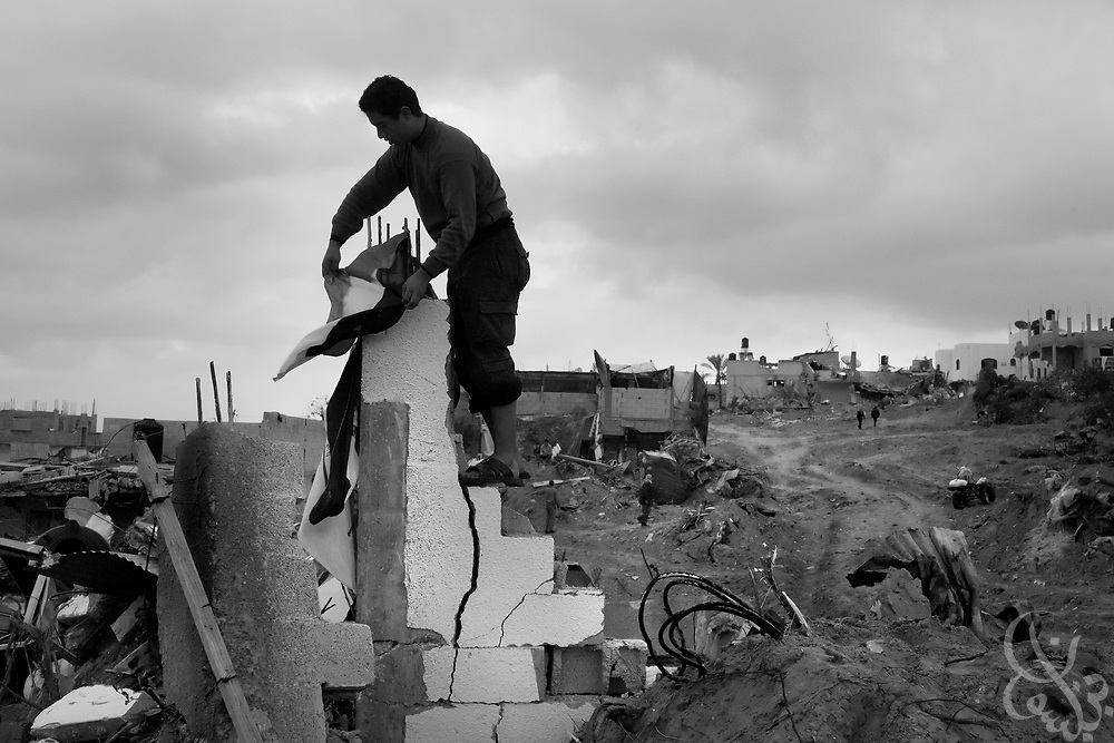 A resident of Beit Lahiya in the northern Gaza strip, places a Palestinian flag atop the rubble of his home that was destroyed during the 21 day Israeli operation against HAMAS inside Gaza January 19,2008. Many residents returned to find destroyed or severely damaged homes from the fighting. According to the United Nations and Palestinian officials, more than 4,000 homes were destroyed during the Israeli operation.