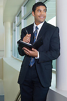 Business man holding diary standing by window in office building