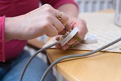 Woman wiring a plug,