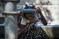 A child drinks from an unpurified well at a primary school near Verrettes, Haiti, Wednesday, November 8, 2017 Photo: Bryan Woolston / @woolstonphoto