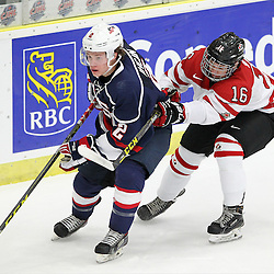 COBOURG, - Dec 15, 2015 -  Game #5 - Canada West vs the United States at the 2015 World Junior A Challenge at the Cobourg Community Centre, ON. Jack Ahcan #2 of Team United States and Brandon Biro #16 of Team Canada West battle for the puck during the first period.(Photo: Tim Bates / OJHL Images)