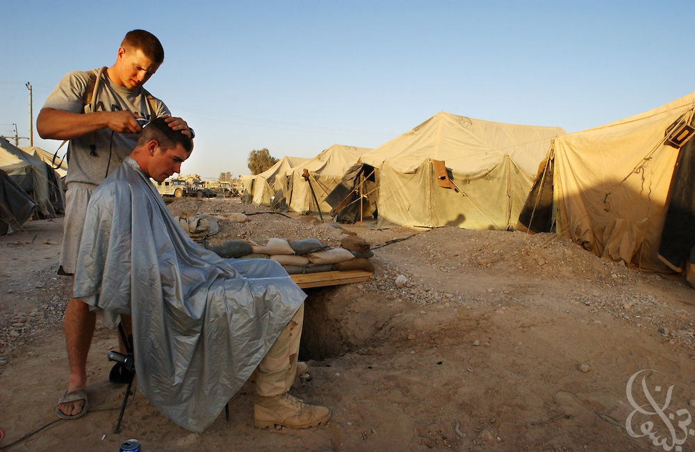 U.S. Army Sgt. Jacob Anderson (L) from Redmond, VA, cuts the hair of fellow 2-187 scout, Spc. Vincent Adler from Troy, IL May 10, 2002 at Kandahar airfield forward operating base in southern Afghanistan. Anderson and Adler's unit has been deployed in Afghanistan since early January as part of Operation Enduring Freedom.