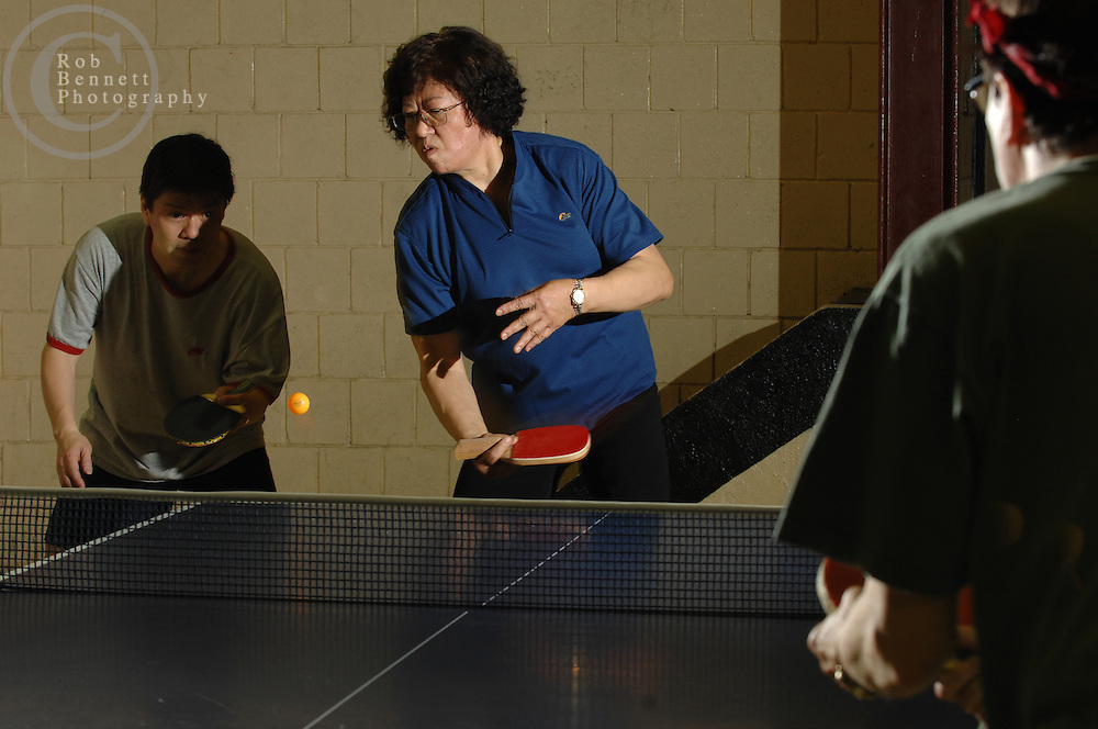Here, Jon Ng (L), a 54-year old Union Representative from the Bronx, and Amy Hsu (C), a 57-year old resident of Hastings, play a doubles match against Steve Zeitlin and Will Shortz (not pictured)...---.The Rivertowns Table Tennis Club is populated by an eclectic mix of characters who spend their days as writers, doctors, cartoonists, crossword editors, nannies, train repairmen, motivational speakers, child psychologists and high school students. These vastly different lives come together for a few hours four nights a week in Tarrytown and Ardsley to engage their common ping pong passion with spirited games and expert instruction in a convivial climate. ..Photographs shot Tuesday night, from 8 to 11pm, at Tarrytown Community Opportunity Center, 105 Wildey Street Tarrytown, NY..