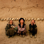 Afghan boys watch as U.S. Air Force planes fly overhead, dropping bombs on nearby Taliban tank positions, kicking off an assault against the Taliban.