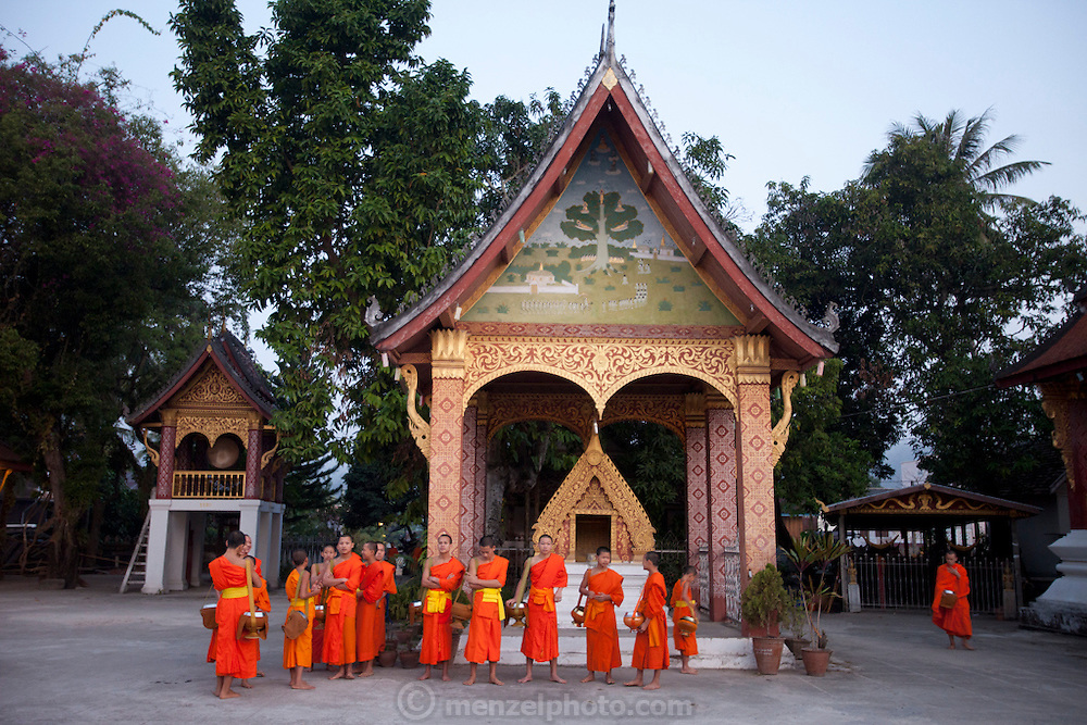 "Luang Prabang, Laos. Every morning at dawn, barefoot Buddhist monks and novices in orange robes walk down the streets collecting food alms from devout, kneeling Buddhists. They then return to their temples (also known as ""wats"") and eat together. This procession is called Tak Bat, or Making Merit. At the Wat Sensoikharam."