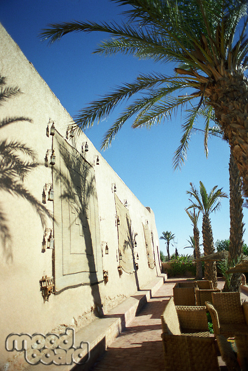 Building exterior with palm trees and wicker furniture