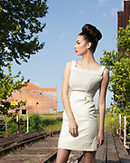 1950s model in vintage dress and hair poses on an old rail bridge behind an abandoned sugar factory