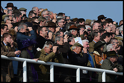 Racegoers watch the first race at the Cheltenham Festival Ladies Day. Cheltenham Racecourse, Cheltenham, United Kingdom. Wednesday, 12th March 2014. Picture by Andrew Parsons / i-Images