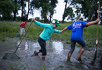 Micah Sheffy-Harris is pulled out of the mud by Terri Danhauer during Summer Orientation About Rivers camp on the Griffith Prairie near Marquette.
