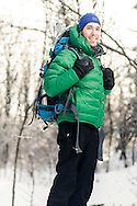 Portrait of a male Hiker backpacking on a winter day trip.