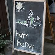 """Blackboard  outdoor restaurant sign """"Happy Friday""""."""