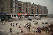 For a story by Dan Levin<br /> FOXCONN<br /> Zhengzhou, June 22nd 2013<br /> Foxconn dorms on a street still under construction.In the span of two years what were rural villages on the outskirt of Zhengzhou has become a bustling factory city dedicated to Foxcoon, and housing 200 000 workers. The city is still expanding with new factories being built.<br /> <br /> Gilles Sabrie for The New York Times