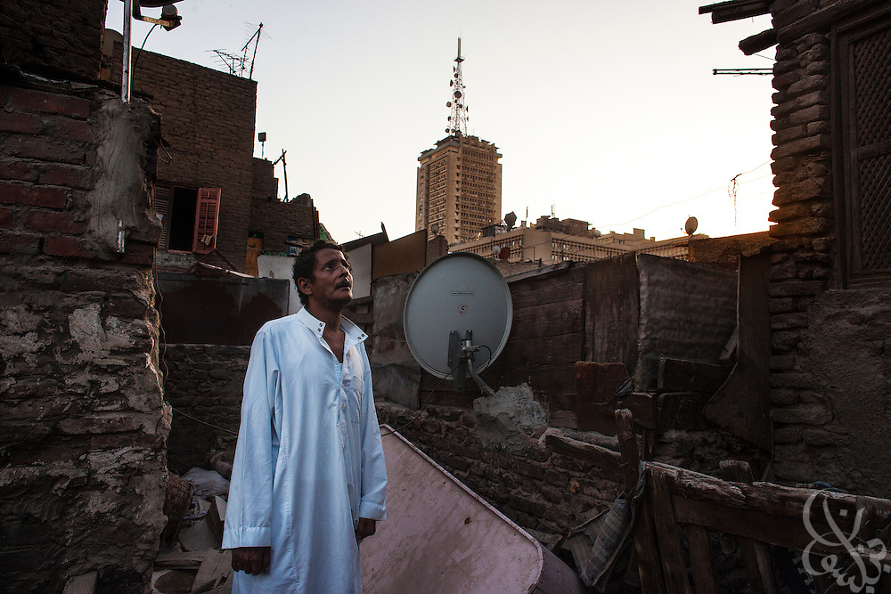 Youseff Ibrahim (age 62), an unemployed Egyptian resident of the Bulaq district of Cairo,  looks out from the rooftop of his dilapidated family home May 22, 2013. Ibrahim's shoddy house is under constant threat of collapse and was ordered demolished five years ago. But like many poor residents of the Bulaq area, he has neither the means to repair it or anywhere else to move with his wife Sania and son Magdy, so the family remains despite the danger.