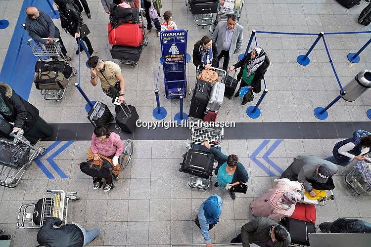 Duitsland, Weeze, 6-5-2017Vlak over de grens ligt het regionaal vliegveld Niederrhein, Weeze, wat in tien jaar uitgegroeid is tot een belangrijke regionale luchthaven en als thuisbasis fungeert voor prijsvechter, chartermaatschappij Ryanair. In de regio bevindt zich ook vliegveld Dusseldorf. Naast passagiersvervoer wordt er veel luchtvracht vervoerd. Passagiers aan de incheckbalie, inchecken.Foto: Flip Franssen