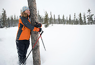 A young woman hugs a tree in a snow covered field in the winter in Bend, Oregon. (releasecode: jk_mr1033) (Model Released)