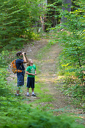 A man and his son birdwatching on a forest trail in Madbury, New Hampshire.